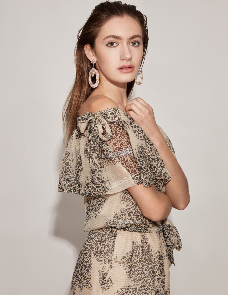 Actress and Singer Nicole Berger, wearing a tan over the shoulder dress and chunky hoops, her hair straight back, one hand clasping a necklace while the other hugs her waist. Body in profile but face is looking straight into the camera. Shot by Beau Nelson